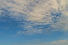 Sparse clouds in the blue sky morning background. Fluffy clouds. In the blue sky evening background. Blue sky in summer background with tiny clouds Royalty Free Stock Images