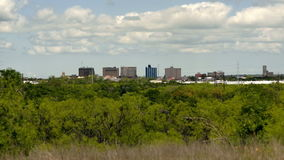 Sparse Downtown City Skyline Wichita Falls Texas Clouds Passing. Wind blows the vegetation and clouds over downtown Wichita Falls stock footage