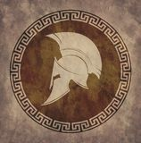 Spartan helmet an icon on old paper in style grunge, is issued in antique Greek style. On the image presented Spartan helmet an icon on old paper in style Stock Photo