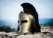 Spartan helmet on rocks. Ancient Spartan helmet with black crest on rocks Royalty Free Stock Images