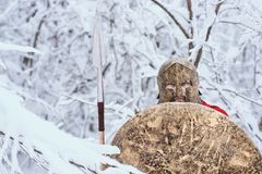 Spartan man took shelter in winter forest. Stock Photo
