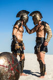 Spartan warrior holding a Roman for his helmet. The Spartan warrior grabbed and held the Roman`s opponent by the helmet Royalty Free Stock Photography