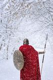 Spartan warrior walks in winter forest in traditional red cape. Royalty Free Stock Photography
