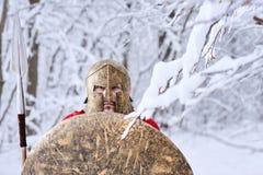 Spartano coraggioso negli sguardi della foresta di inverno in camera Immagine Stock