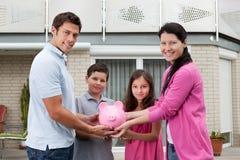 Sparungskonzept - glückliche Familie mit piggy Querneigung Stockfotografie