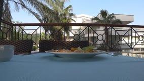 Sparvar stjäler besökaremat från plattan, som står på tabellen, på terrassen av restaurangen stock video