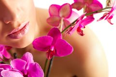 Nätt härlig avslappnande kvinna med purpurfärgade orchids royaltyfri bild