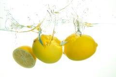 Spash de tres limones en agua en el fondo blanco foto de archivo