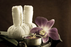 SpaSpa herbal compressing ball with candles and orchid Royalty Free Stock Photos
