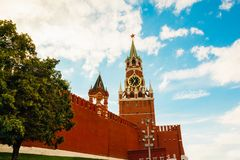 Part of the wall near the Kremlin Spasskaya tower with chimes. Spasskaya Tower of of the Kremlin chimes, red wall and a tree Stock Photography