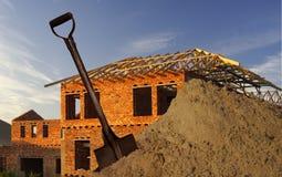 Spaten, Sand und Haus Stockfoto