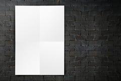 Spatie het gevouwen document affiche hangen op zwarte bakstenen muur, Malplaatje m Stock Afbeeldingen