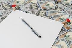 Spatie met een pen op het geld stock afbeeldingen