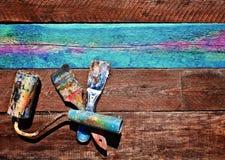 Spatola, rullo e spazzola su un fondo di legno Vecchia t di verniciatura fotografia stock