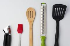 Spatola Zester del cucchiaio della spazzola della stampa di aglio sul raccolto bianco del fondo Fotografie Stock