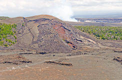 Spatter Cone of a Hawaiian Volcano. Spatter Cone of Kilauea Iki in Hawaii, with steam from the main volcano in the background Stock Photos