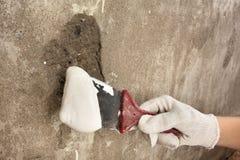 Spatula εκμετάλλευσης χεριών με το ασβεστοκονίαμα Στοκ φωτογραφία με δικαίωμα ελεύθερης χρήσης