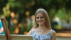 Το όμορφο κορίτσι σύρει μια εικόνα στο πάρκο χρησιμοποιώντας μια παλέτα με τα χρώματα και spatula Easel και καμβάς με μια εικόνα απόθεμα βίντεο