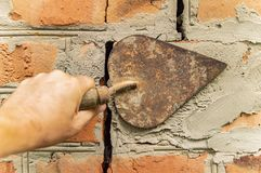 Spatula in the hand of the builder - repair of a brick wall stock photo