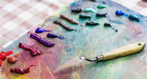 spatula for painting on a palette of paints used, blurred focus stock photography