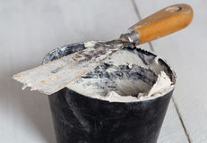 Spatula with plaster and mixing tub Stock Image