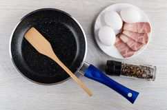 Spatule dans la poêle, pot avec le condiment, oeufs, poitrine dans le plat sur la table Vue sup?rieure photos stock