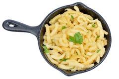 Spatzle dans une casserole avec du beurre et le persil sur le fond blanc Image libre de droits