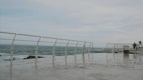 Spaventato da una grande onda del mare sul lungomare stock footage