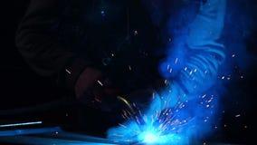 Spawacz pracuje w masce w zwolnionym tempie Iskry latają w różnych kierunkach Błękitny kolor łuny spaw Praca z stalą