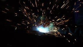 Spawacz pracuje w zmroku przy budynkiem Mężczyzna spawa szczegóły żelazny projekt Jaskrawe iskry od spawu w strzale zbiory