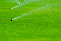 Spaying νερό ψεκαστήρων χορτοταπήτων πέρα από την πράσινη χλόη Σύστημα άρδευσης Στοκ φωτογραφία με δικαίωμα ελεύθερης χρήσης