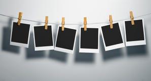Spazii in bianco della pellicola del Polaroid sulla corda Fotografia Stock