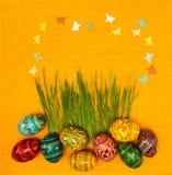 Spazio in bianco, accogliente la carta di pasqua con le uova di Pasqua e l'erba verde sopra Fotografia Stock