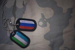 spazio in bianco dell'esercito, medaglietta per cani con la bandiera della Russia e l'Uzbekistan sui precedenti cachi di struttur Immagine Stock Libera da Diritti