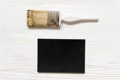 Spazio in bianco e pennello di carta neri su fondo di legno Modello per la cartolina d'auguri Immagine Stock