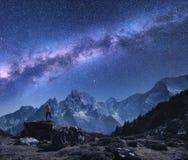 Spazio con la Via Lattea, uomo sulla pietra e montagne immagine stock