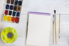 Spazio creativo Lo spazio di lavoro dell'artista sulla tavola misera: l'acquerello della pittura, taccuino, spazzola fotografia stock