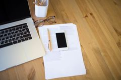 Spazio di funzionamento con il computer portatile aperto, il telefono cellulare moderno ed i documenti cartacei Fotografie Stock Libere da Diritti