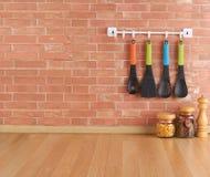 Spazio vuoto sul contatore di cucina con gli utensili sui ganci fotografie stock