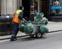 Spazzino che spinge il suo carrello con le borse Immagini Stock Libere da Diritti