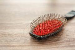 Spazzola con capelli persi sulla tavola di legno Fotografia Stock