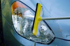 Spazzola con il bastone che lava un'automobile blu Immagine Stock Libera da Diritti