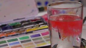 Spazzola dell'acquerello immersa in acqua archivi video
