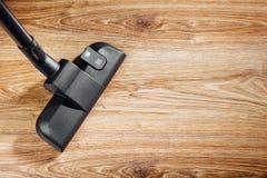 Spazzola dell'aspirapolvere sul pavimento di legno Fotografia Stock