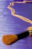 Spazzola della mascara con la catena dorata sopra seta blu Immagine Stock