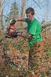 Spazzola di schiarimento del giovane con la sega a catena Fotografie Stock Libere da Diritti