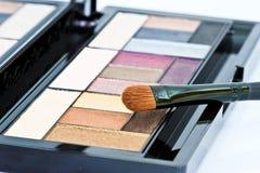 Spazzola e cosmetici, su un fondo bianco  Immagine Stock
