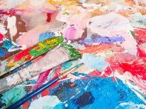 Spazzola e tavolozza luminosa della petrolio-pittura per fondo Fotografia Stock