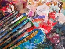 Spazzola e tavolozza luminosa della petrolio-pittura per fondo Immagini Stock