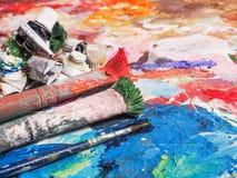 Spazzola e tavolozza luminosa della petrolio-pittura per fondo Immagini Stock Libere da Diritti